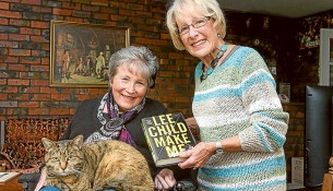 Page turner: Molly the cat settles down with owner Helen Latham, left, for another thriller delivered by library volunteer Adele Parker. Picture: Gary Sissons