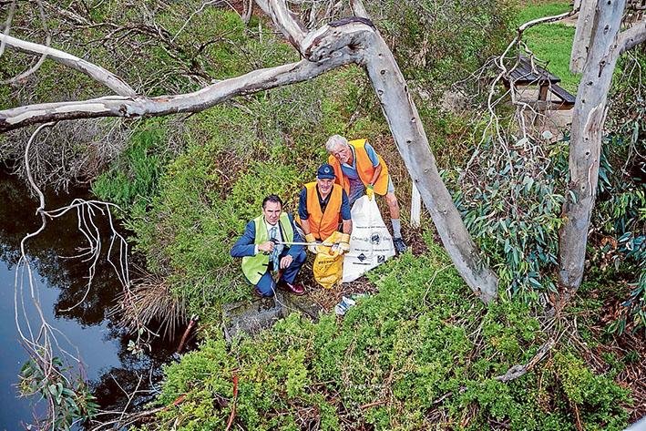 On the litter lookout: Mayor James Dooley, left, and Kananook Creek Association members Paul Davies and Trevor Nock tidy up around Kananook Creek. Picture: Yanni