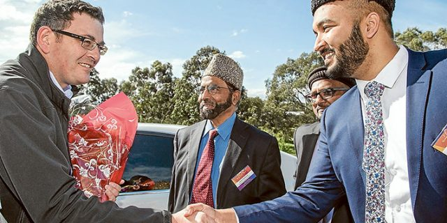 Peaceful meeting: The Premier Daniel Andrews is greeted by Imam Wadood Janud, right, on his arrival at a peace symposium at the Bait-ul-Salam mosque in Langwarrin. Ahmadiyya Muslim Community Australia national president Imam Inam-ul-Haq Kauser is in the centre. Top left, children of mosque members singing the national anthem. Pictures: Gary Sissons